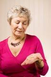 Senior older lady holding tablets or pills Stock Image