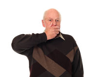 Senior older man covering mouth Stock Image