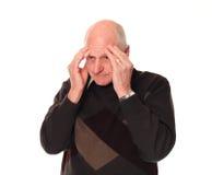 Senior older man holding head with stress headache. Senior older retired man on white background holding his head with a stress headache royalty free stock photos