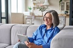 Free Senior Older Woman At Home At Video Meeting With Family Friends On Tablet. Stock Images - 216450754