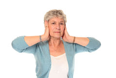 Senior older woman covering ears Stock Image
