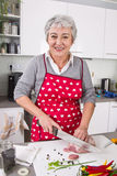 Senior or older woman with grey hair cooking in kitchen. Senior or older woman with grey hair cooking fresh meat in kitchen Royalty Free Stock Images