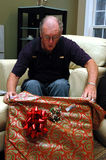 Senior opening gift. A surprised senior man opening a  present Royalty Free Stock Photography