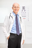 Senior optician posing in his office. Vertical shot of a senior optician in a white coat posing in his office in front of an eyesight test and smiling royalty free stock photography