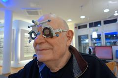 Senior at the optician testing new lenses in a trail frame royalty free stock image