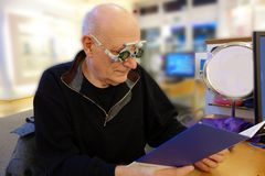 Senior at the optician tries to read with new glasses stock photography