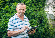 Senior outdoor with tablet PC Stock Image