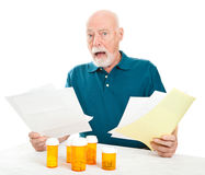 Senior Overwhelmed by Medical Costs. Senior man overwhelmed by the cost of his medical care and prescription drugs.  White background Royalty Free Stock Images