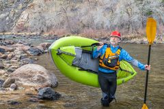 Senior paddler carrying  inflatable whitewater kayak stock photography