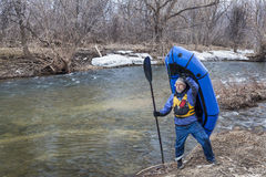 Senior paddler carrying a packraft royalty free stock image