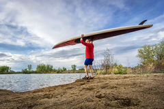 Senior paddler carrying paddleboard. Senior male paddler carrying his SUP paddleboard on a lake shore in Colorado, early spring Stock Photo