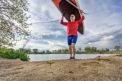 Senior paddler carrying paddleboard Stock Photo