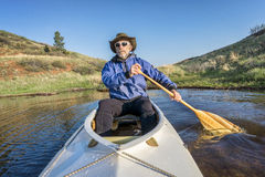 Senior paddler and expedition canoe. Senior paddler in a decked expedition canoe on Horsetooth Reservoir, Fort Collins, Colorado, springtime scenery stock images