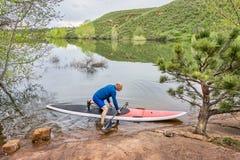 Senior paddler launching paddleboard Stock Photo