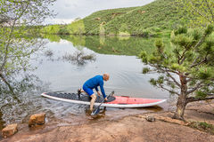 Senior paddler launching paddleboard. Senior male paddler launching his red SUP paddleboard at a rocky lake shore (Horsetooth Reservoir, Fort Collins, Colorado Stock Photo