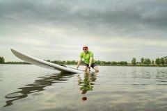 Senior paddler on stand up paddleboard. Senior male paddler on a paddleboard, lake in northern Colorado,  clody summer morning Stock Image