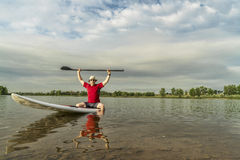 Senior paddler on stand up paddleboard. Senior male paddler sitting on a paddleboard, lake in northern Colorado with an early summer scenery Stock Photo