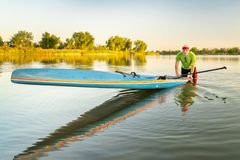 Senior paddler with stand up paddleboard stock image