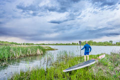 Senior paddler with SUP paddleboard watching stormy sky Royalty Free Stock Image