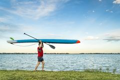 Senior paddler walking with a stand up paddleboard royalty free stock image