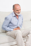 Senior in pain sitting on sofa. Elderly man suffering from stomachache Stock Photo