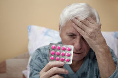 Senior with painkillers Stock Photos