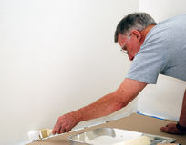 Senior Painter. A view of an elderly man painting the border of a garage floor Royalty Free Stock Photos