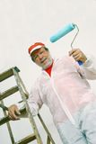 Senior painter. Smiling senior painter with rollerpaint, ladder and white outfite Stock Image