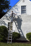 Senior Painting House. Senior citizen (Man) high on ladder painting house with his full body shadows casted on wall Stock Photography