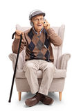 Senior with pair of headphones and cane in an armchair royalty free stock images
