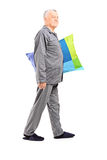 Senior in pajamas walking and holding a pillow. Full length portrait of a senior in pajamas walking and holding a pillow isolated on white background Royalty Free Stock Photography