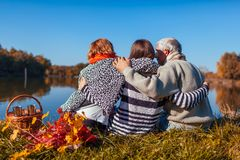 Senior parents relaxing by autumn lake with their adult daughter. Family values. People having picnic stock photos