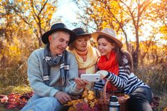 Senior parents using smartphone in autumn forest with their daughter. Family values. People having picnic royalty free stock photography