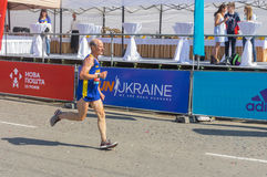Senior participant hurrying to finish line during Interipe  Dnipro Half Marathon race on the city street Royalty Free Stock Photos