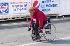 Senior participant in a wheelchair hurrying to finish line royalty free stock photos