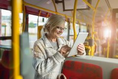 Senior woman using tablet, while riding public bus stock photos