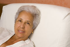 Senior patient in bed. Elderly patient lying in bed at home Stock Photography