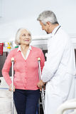 Senior Patient Being Assisted By Doctor With Crutches. Smiling senior female patient being assisted by mature doctor with crutches at rehab center Royalty Free Stock Image