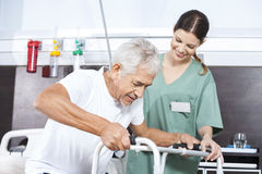 Senior Patient Being Assisted By Female Nurse In Using Walker Stock Photos