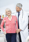 Senior Patient Being Helped By Doctor With Crutches. Smiling senior female patient being helped by mature doctor with crutches at rehab center Royalty Free Stock Images