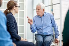 Senior Patient Communicating with Psychologist. Portrait shot of senior patient communicating with highly professional psychologist while participating in group Royalty Free Stock Photo