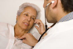 Senior patient with a doctor. Male doctor listening with stethoscope to senior patient's heart and lungs Royalty Free Stock Images
