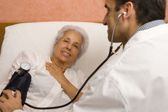 Senior patient with a doctor. Senior patient is being observed by doctor - measuring blood pressure Royalty Free Stock Photo