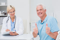 Senior patient gesturing thumbs up by doctor in clinic. Portrait of senior patient gesturing thumbs by doctor in clinic Stock Image