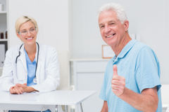 Senior patient gesturing thumbs up while doctor looking at him. Portrait of happy senior patient gesturing thumbs up while doctor looking at him in clinic Stock Images