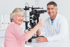 Senior patient gesturing thumbs up while sitting with optician Stock Images
