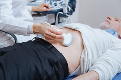 Senior patient getting ultrasound scanning of abdomen in the clinic Royalty Free Stock Image