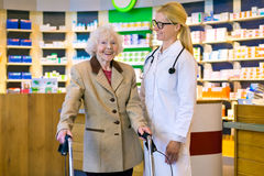 Senior patient happy with her smiling doctor. Happy senior female patient standing with smiling doctor with pony tail and eyeglasses in front of pharmacy counter Royalty Free Stock Image