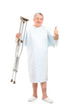 Senior patient holding crutches. Full length portrait of a senior patient holding crutches and giving thumb up  on white background Royalty Free Stock Images
