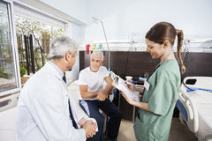 Senior Patient Looking At Doctor While Nurse Holding Reports Stock Photography